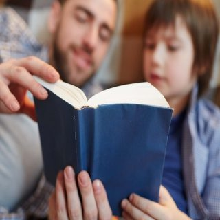 Open book with blue cover held by father and son